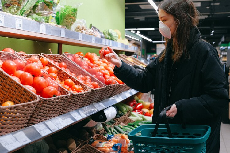 Woman shops for vegetables in grocery store wearing a mask