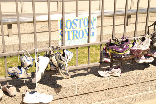 """Fence with """"Boston Strong"""" sign posted on it as well as sneakers draped on the fence by their laces tied together."""