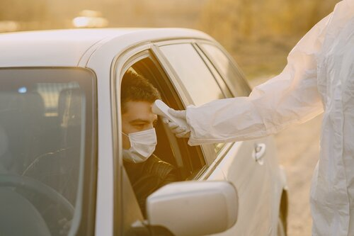 Man gets his temperature taken while in a car and wearing a mask