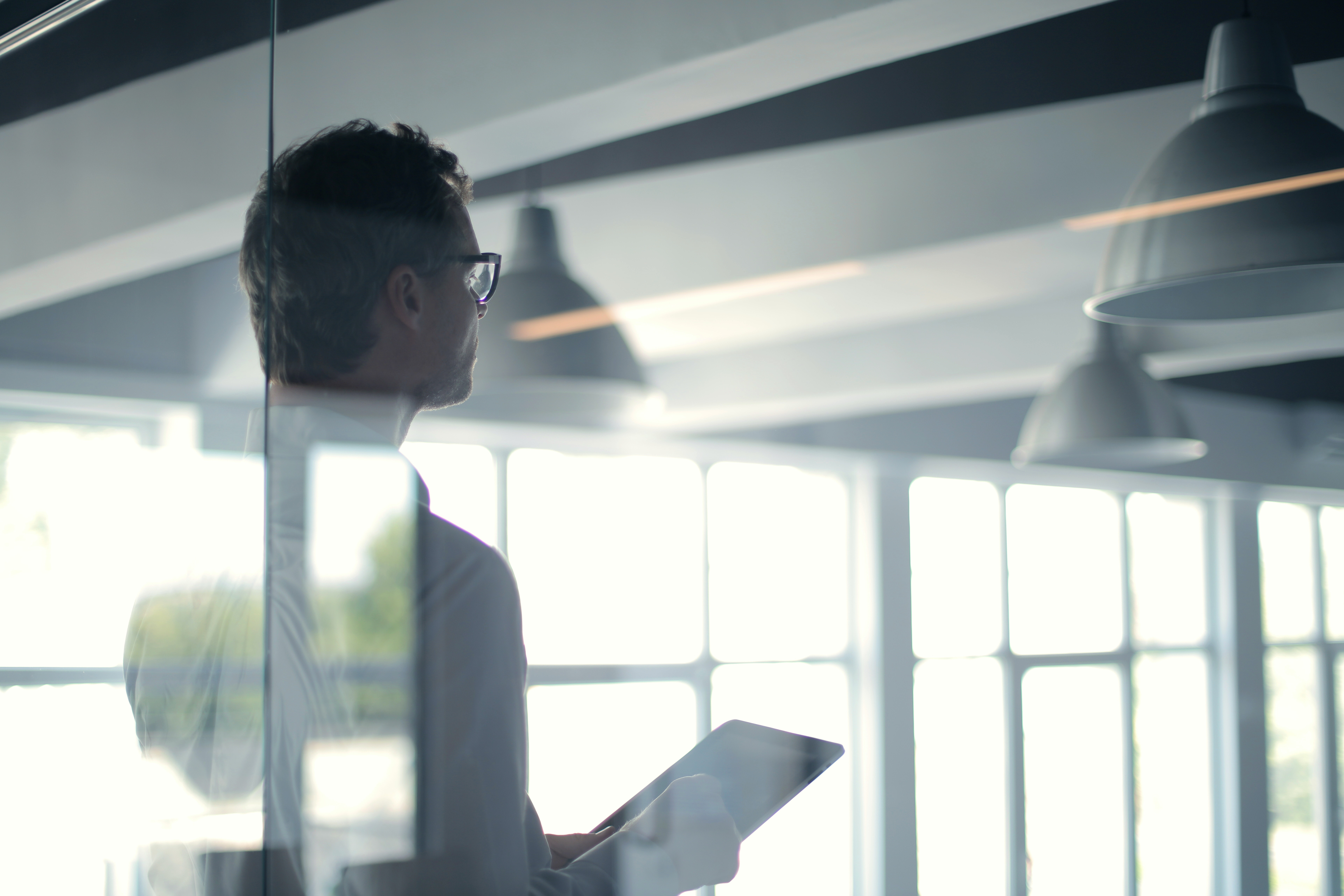 Man behind glass in office conference room