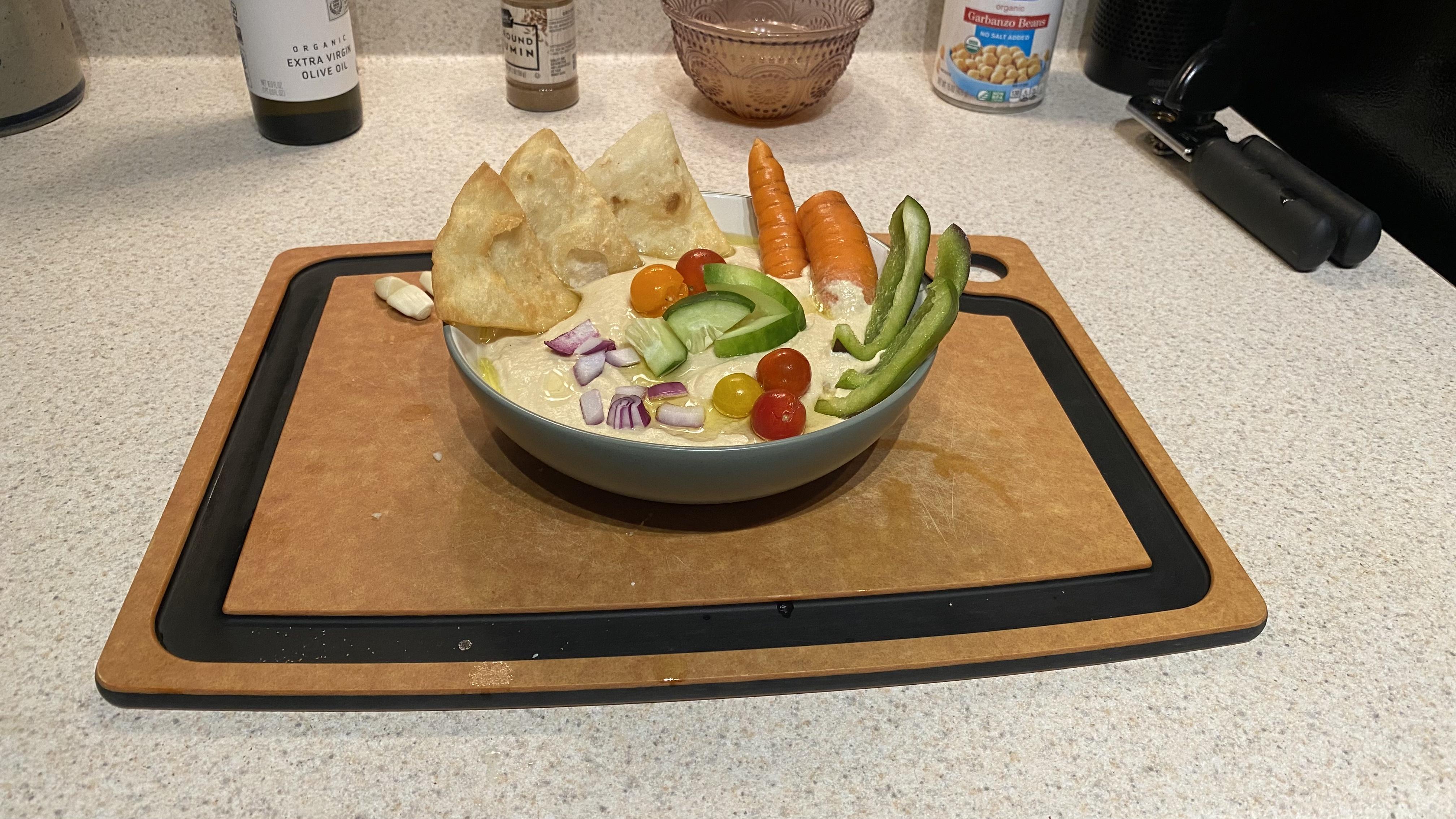 A bowl of homemade hummus full of freshly-cut veggies!