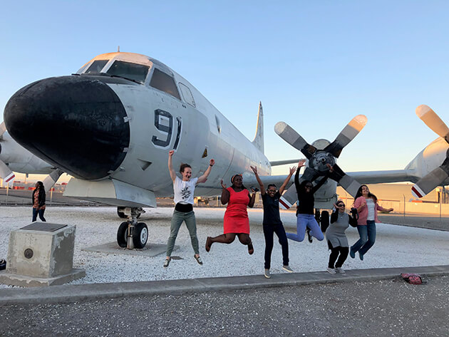 People posing in front of an airplane