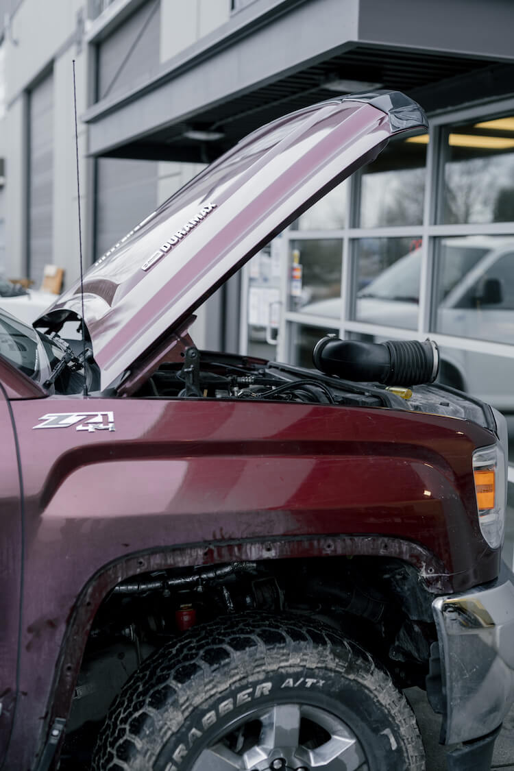 Duramax Z71 with the hood up out front of the diesel repair shop