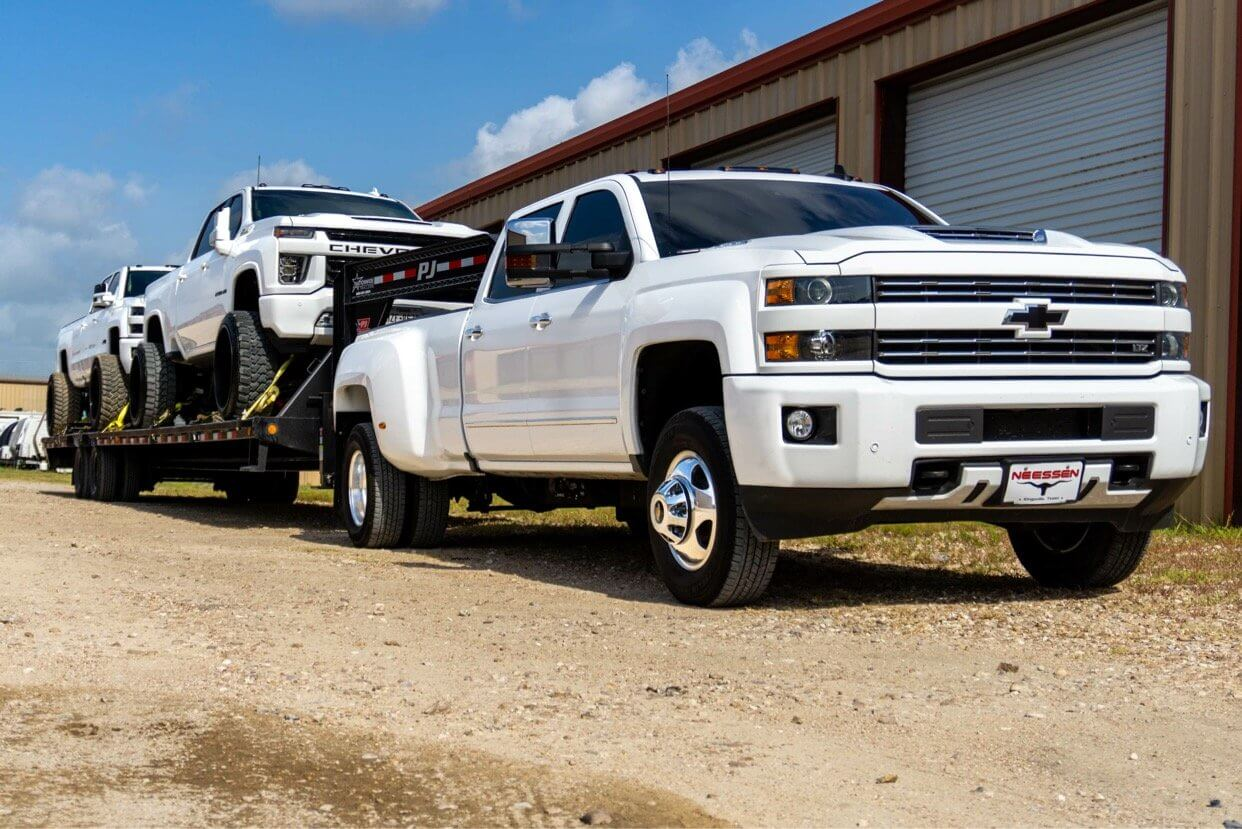 Chevy Silverado HD towing trucks in front of the shop