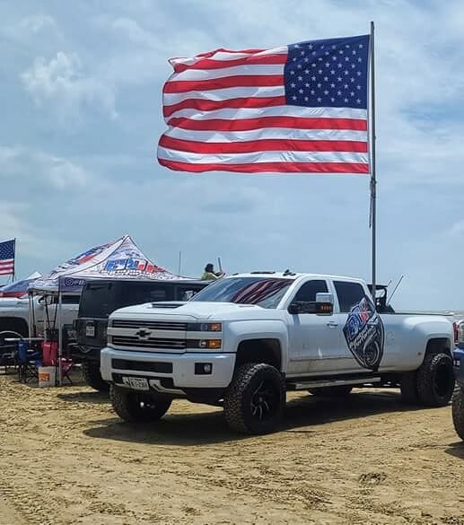 Burntout Diesel Performance mascot truck at the beach under an American flag