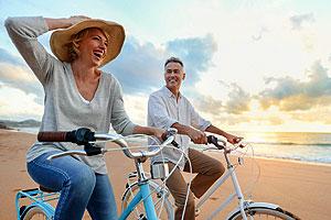 Active couple riding bikes on beach