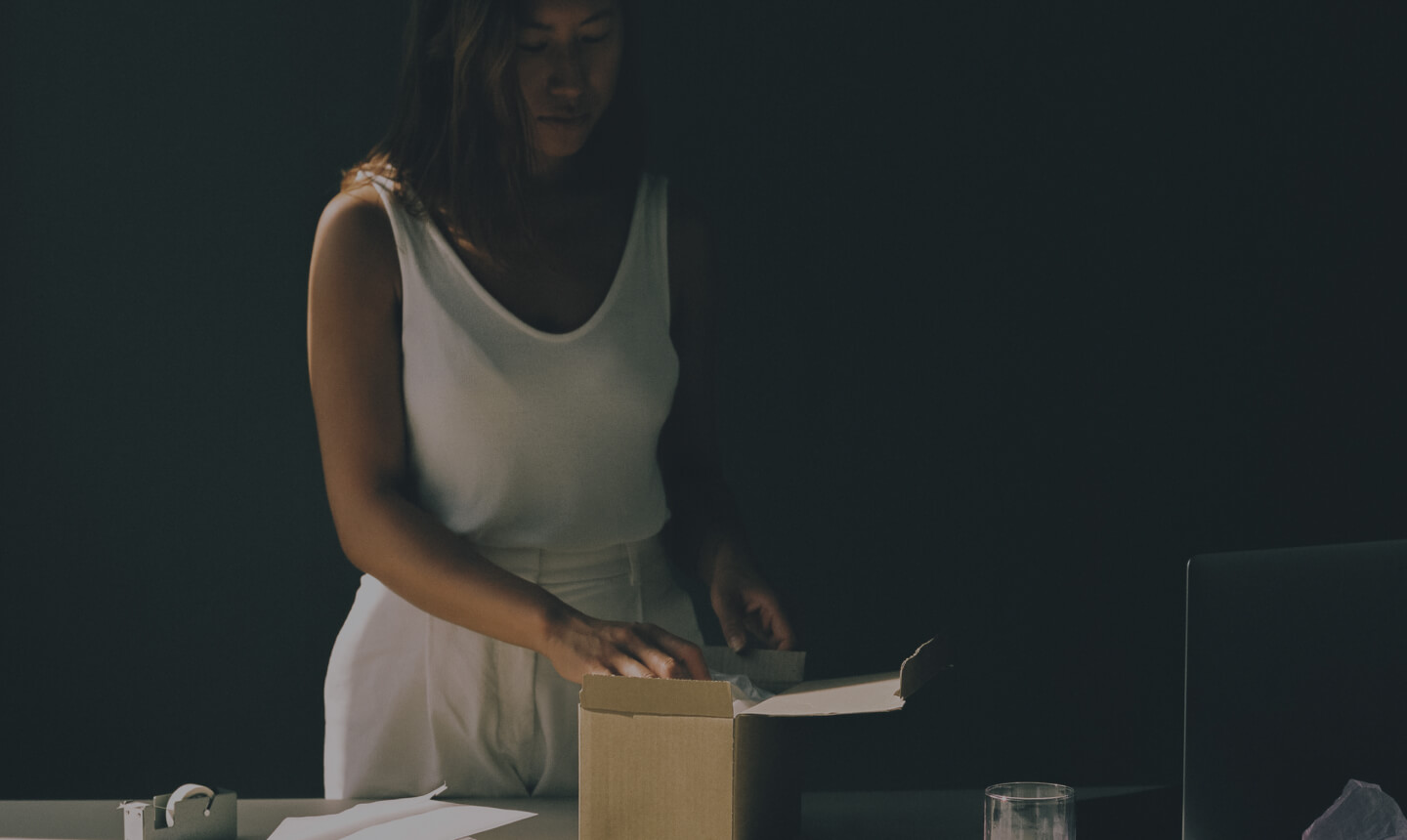 Woman in a white dress unpacking glasses