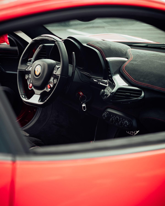 Red car photo view showcasing clean interior through passenger window