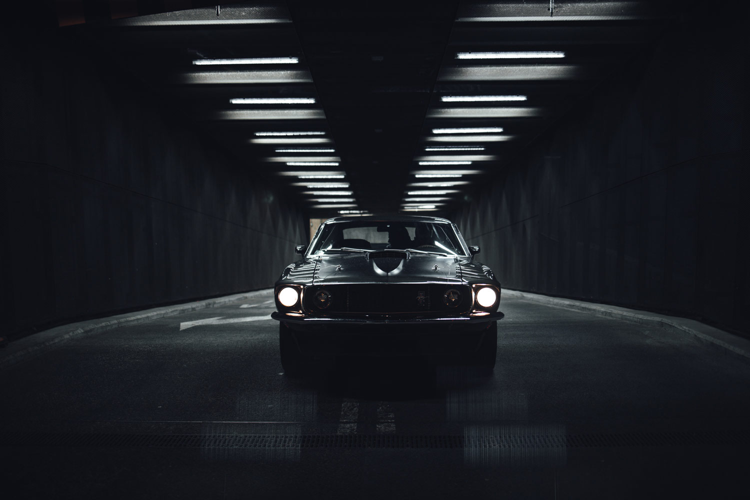Wide angle photo of car in darkness with big lights