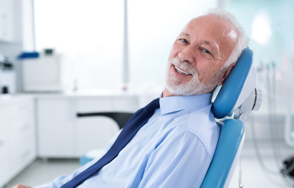 Man sitting on  a surgical dental chair smiling