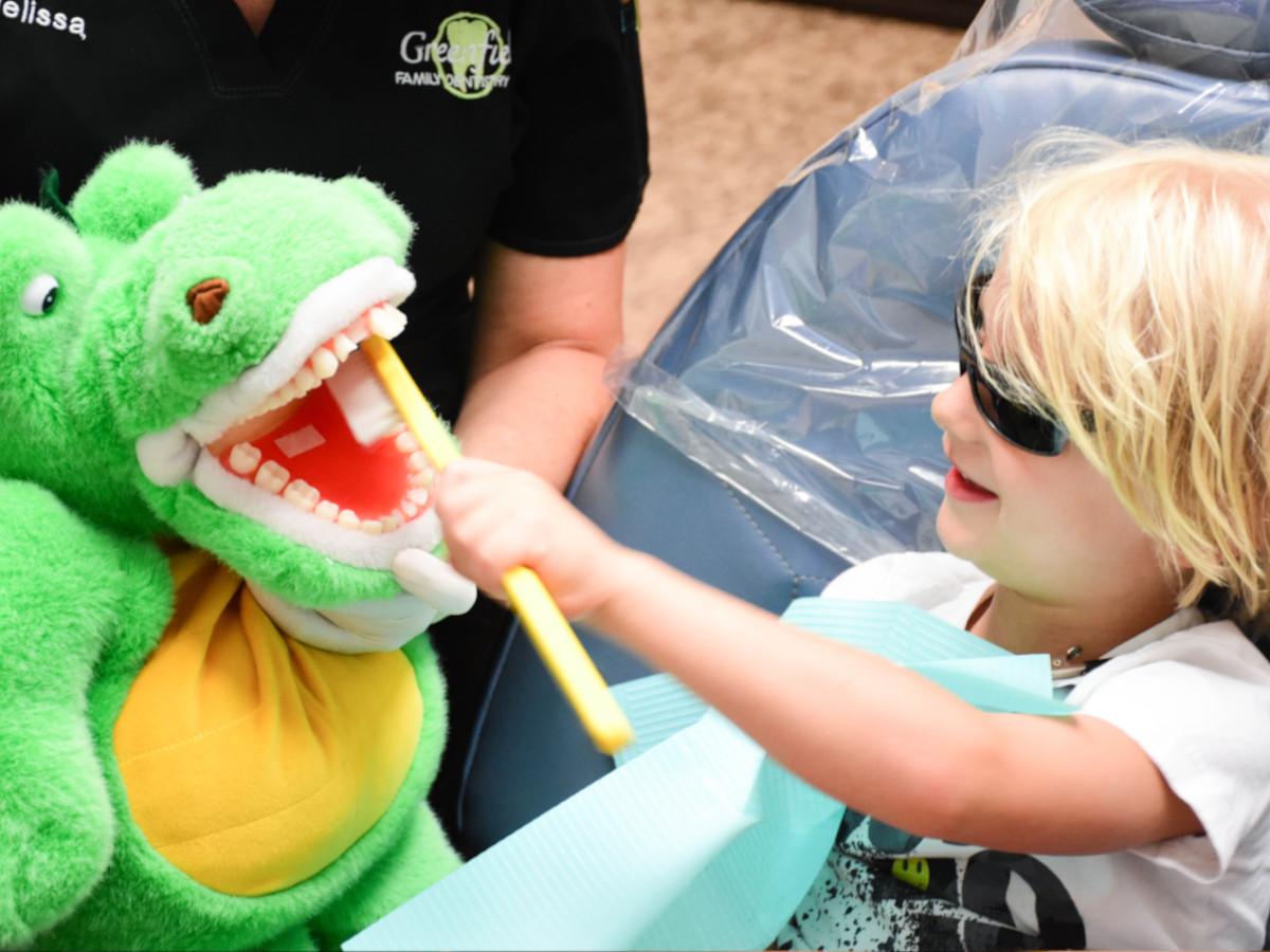 Child brushing crocodile plush teeth