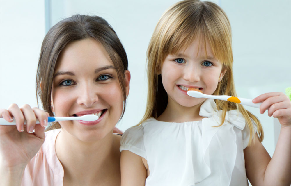 Mom and child brushing their teeth