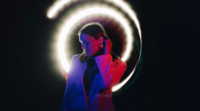 A woman in front of a black background, lit with pink and blue neon lighting