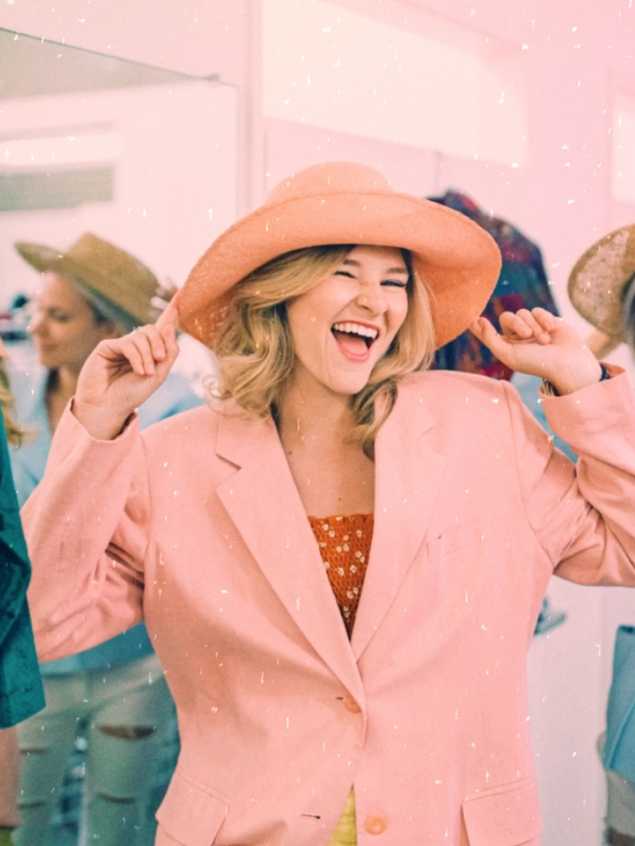 A girl in a pink suit jacket and big hat smiles for the camera, filtered with Zach Lower's sunset look