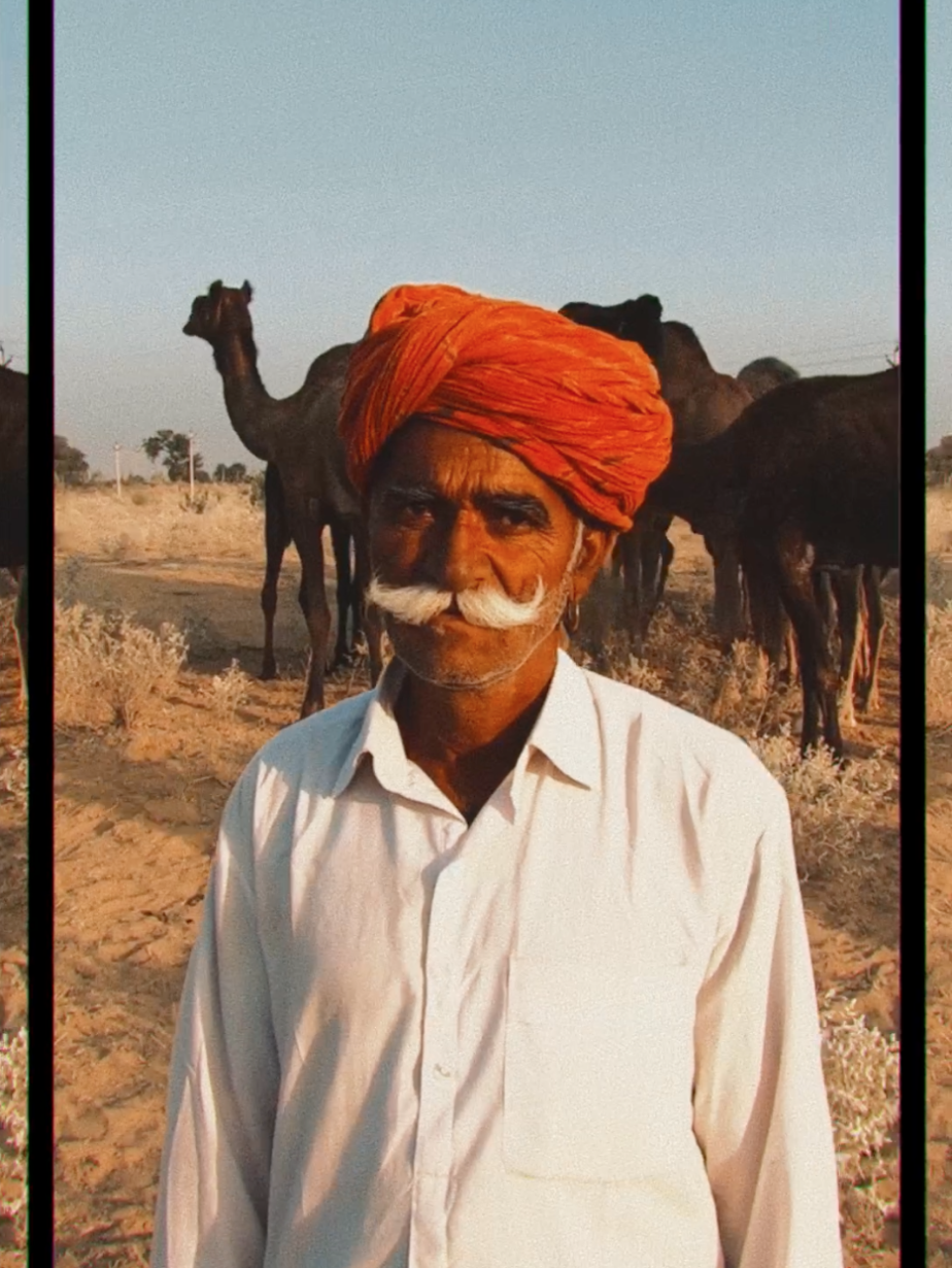 A man in an orange turban looks at the camera, shot with Mike's Varna look