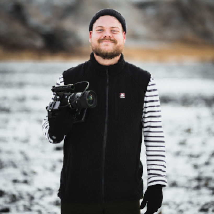 Zach Lower smiling with a camera in hand
