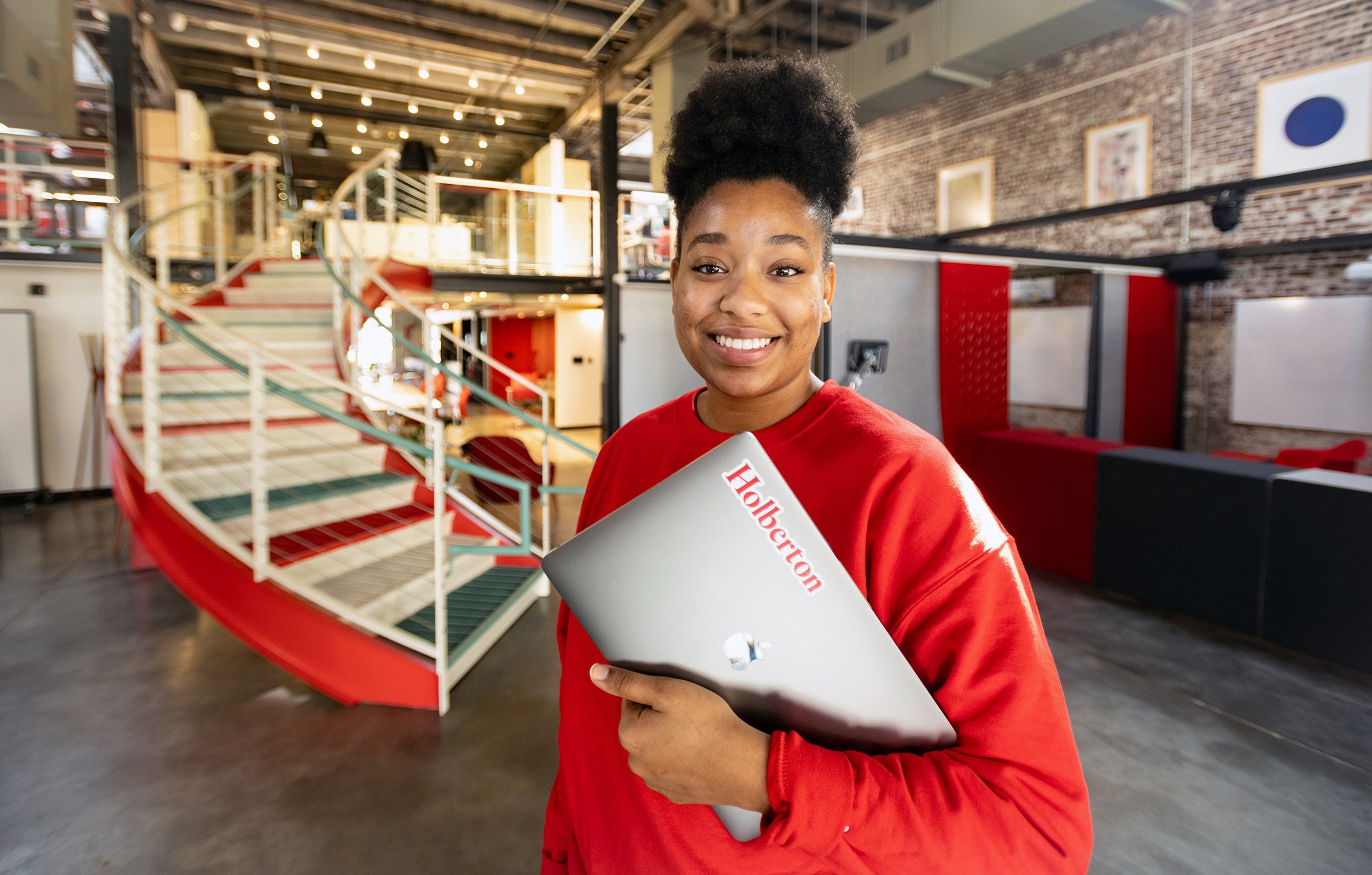 holberton school student facing the camera holding her computer.