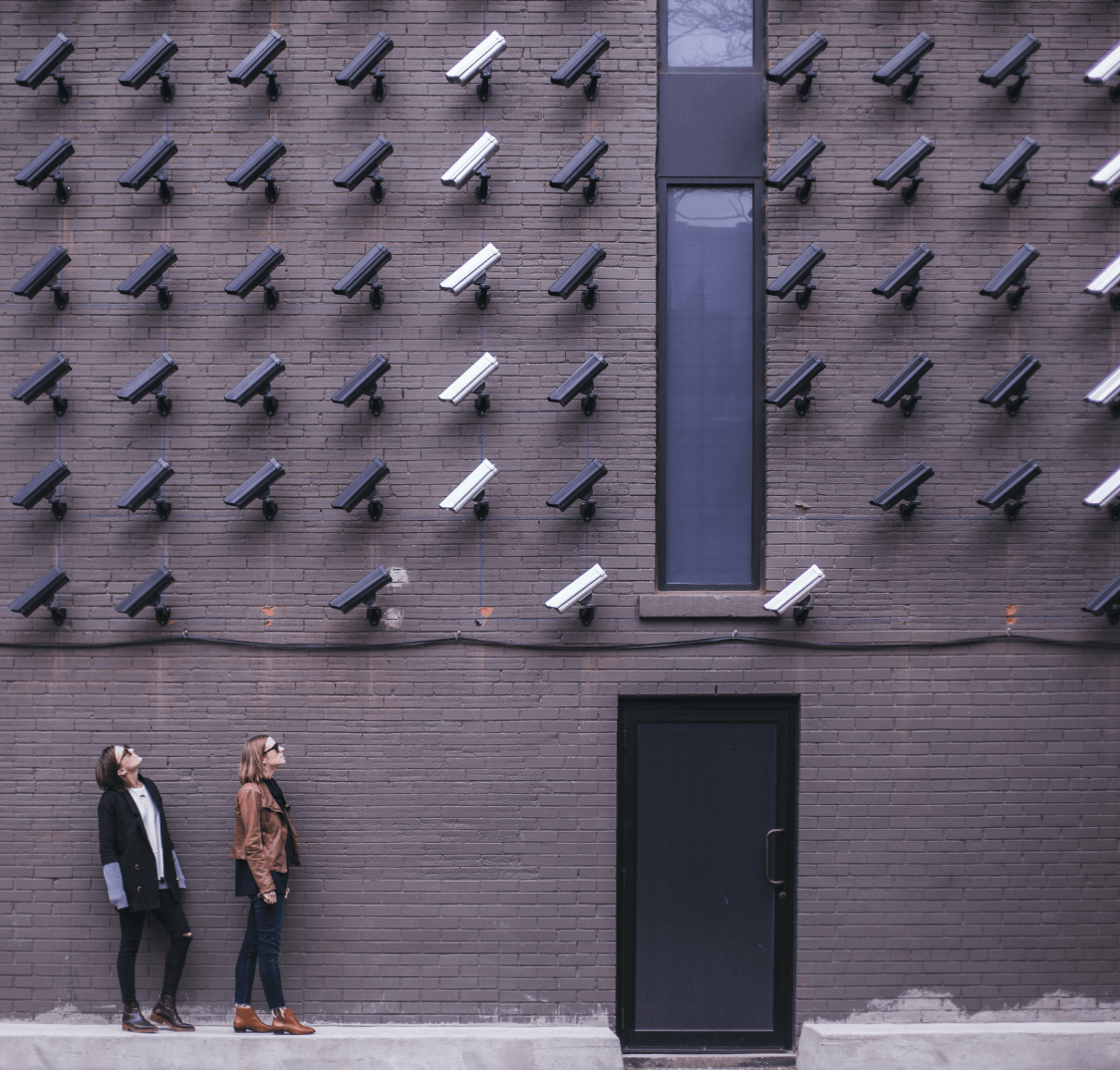 People looking at a wall of cameras