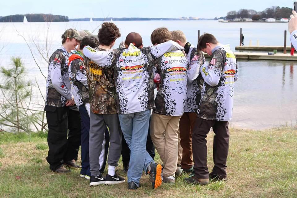 The Riley's Catch team huddled in prayer