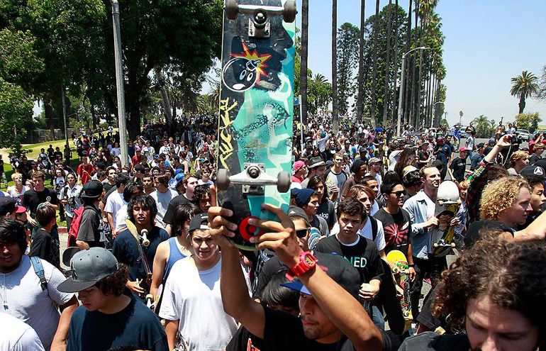 crowd of people with man holding skateboard with adam bomb logo on it