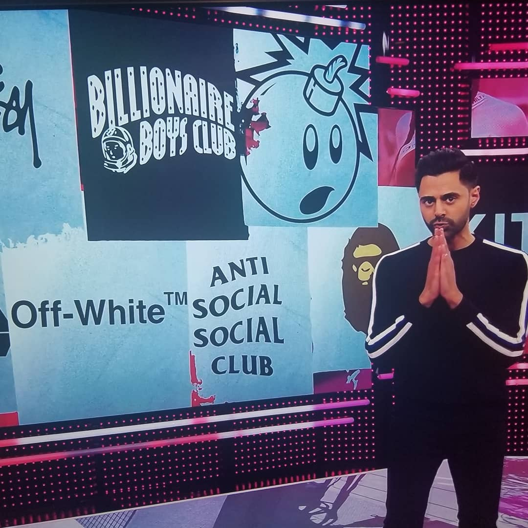 talk show host standing next to street wear logos with adam bomb logo on it