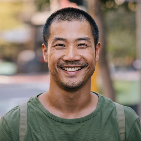 a man standing and smiling outside