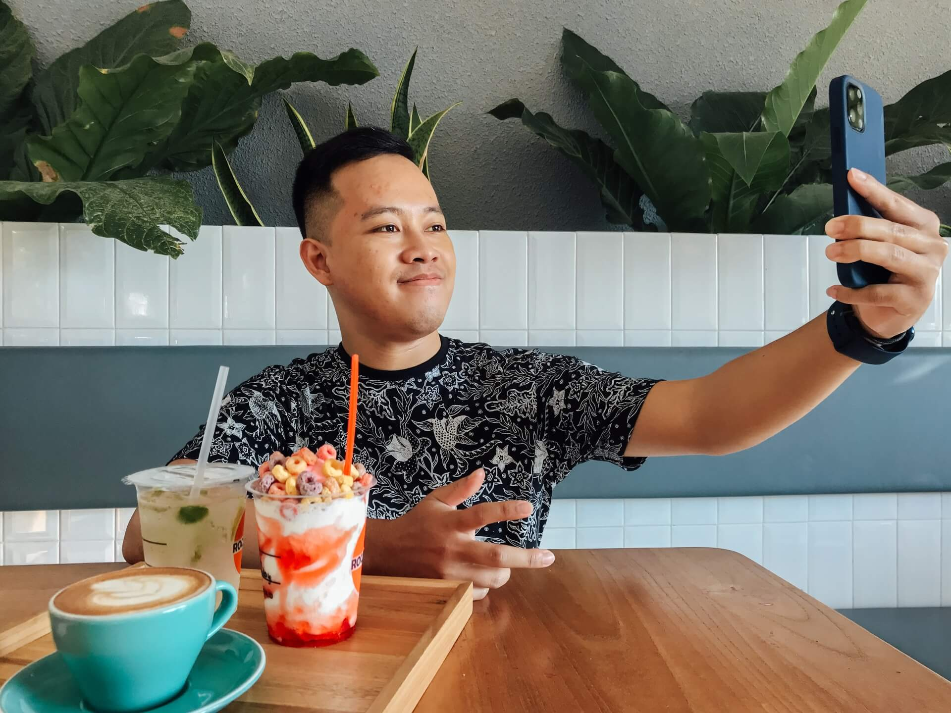 Young man streaming with a cellphone in a restaurant while having a milkshake and cappuccino