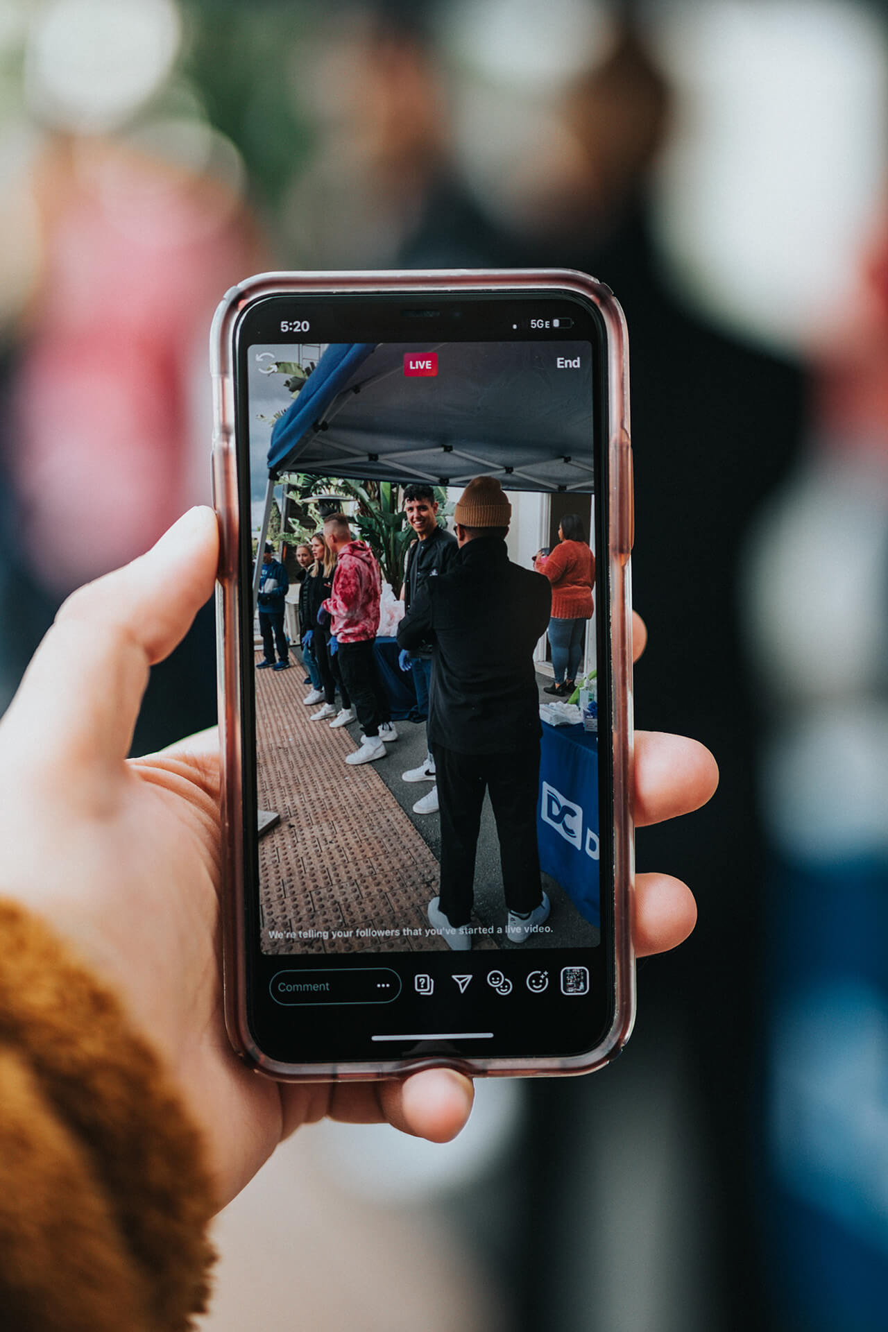 Livestream event being broadcasted from a phone. The event depicts people chatting in a queue