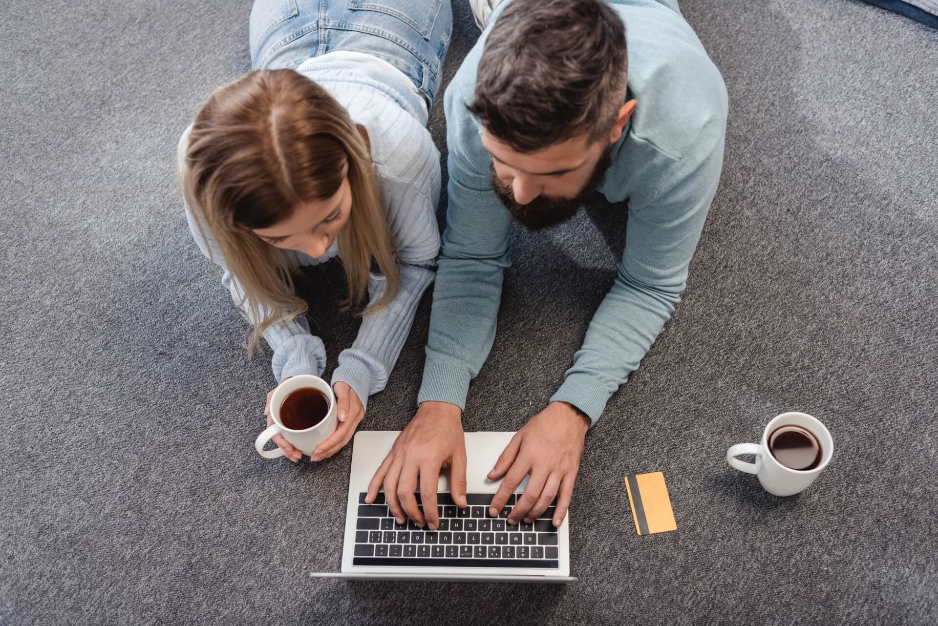 A couple lie on the floor on their laptop with two cups of coffee