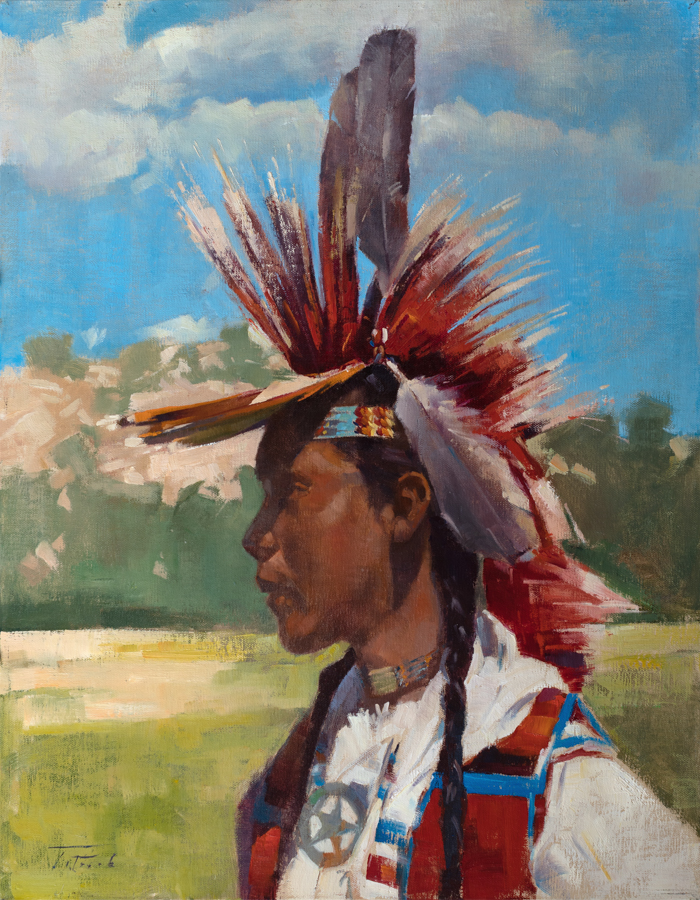 Young Native American wearing headdress with feathers, shown in landscape under big blue sky.