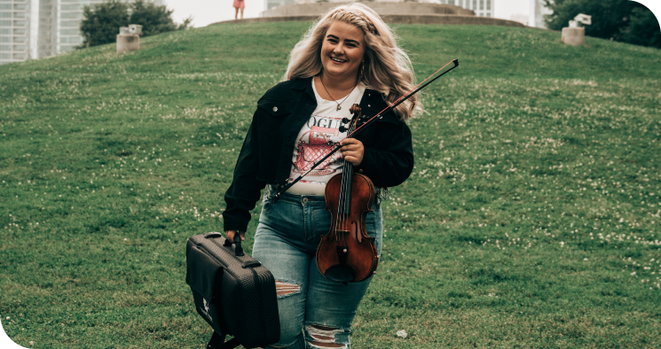 Trala student holding her violin.