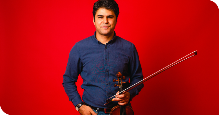 Trala Instructor holding his violin.