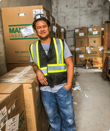 Warehouse worker on uniform  standing leaning on cardboard boxes