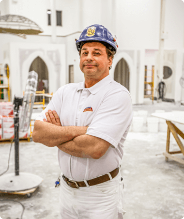 A man in a helmet standing in front of a large room where repair work is going on