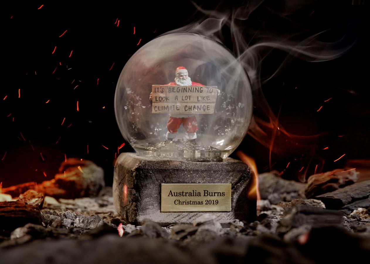 """A snow globe filled with ash and Santa holding a sign that says """"It's beginning to look a lot like climate change"""""""