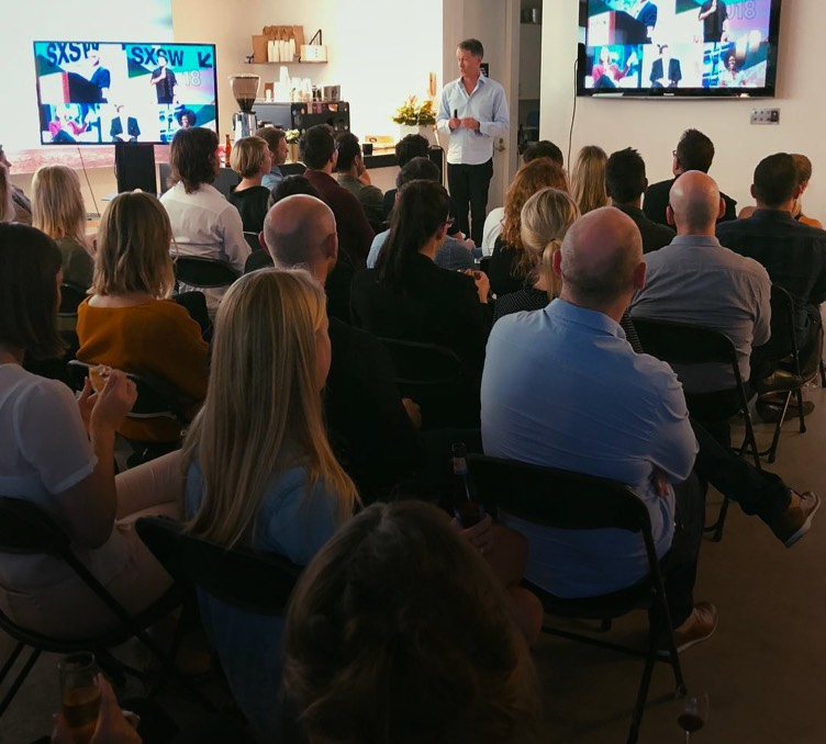 A man presenting insights from SXSW to interested clients and staff.