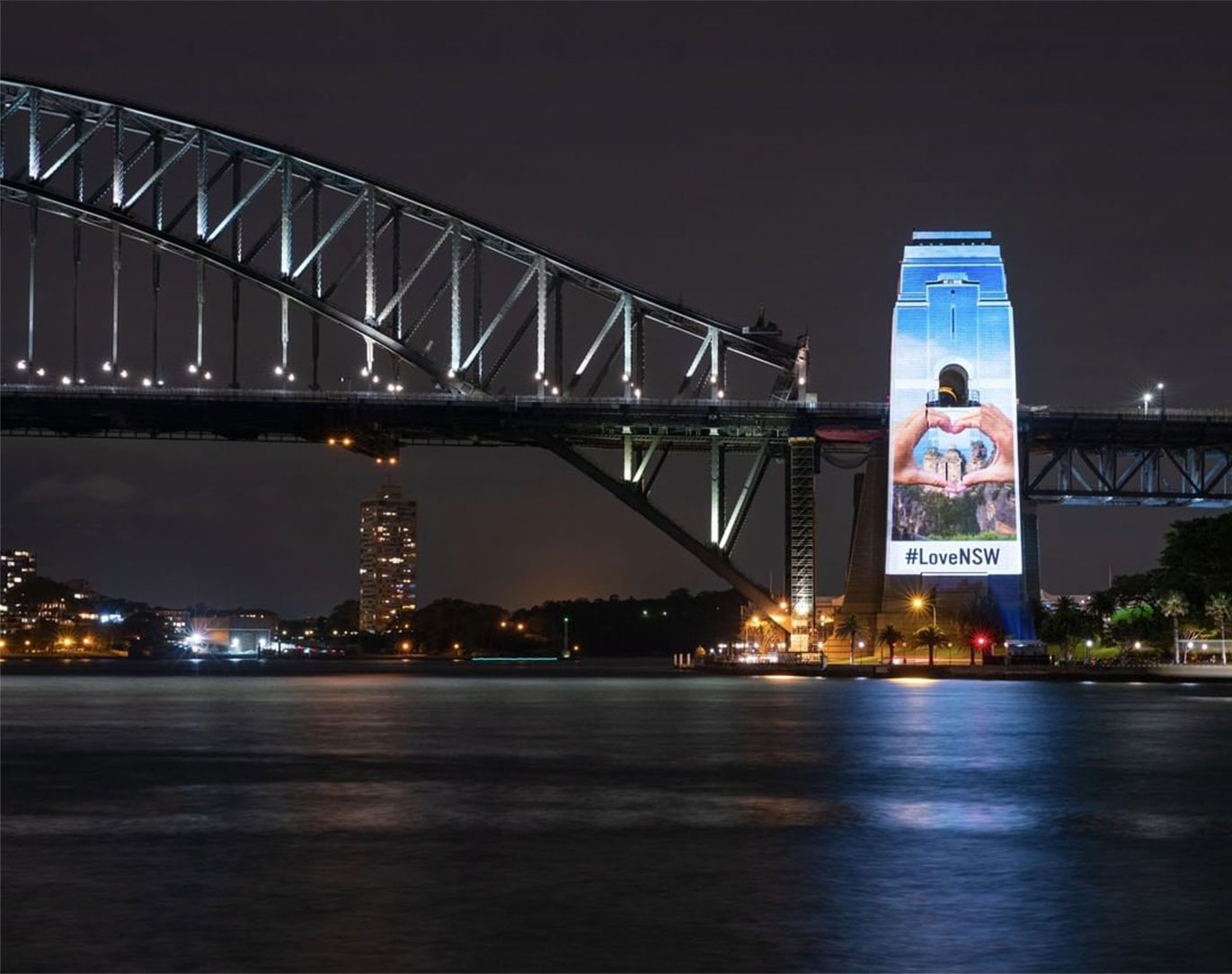 An image of the Sydney Harbour Bridge with a projection on the pylon saying #LoveNSW