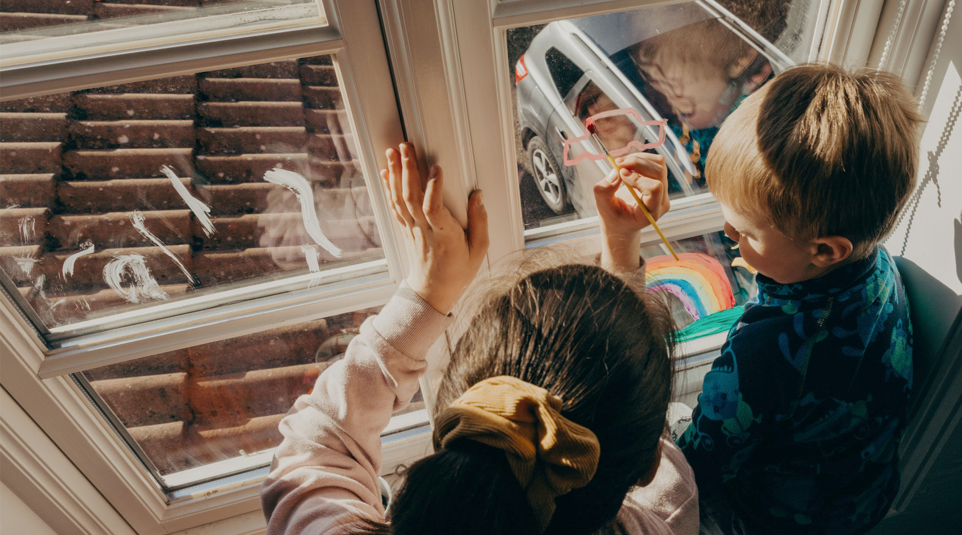 Children painting colourful pictures on their bedroom window so others can enjoy the imagery