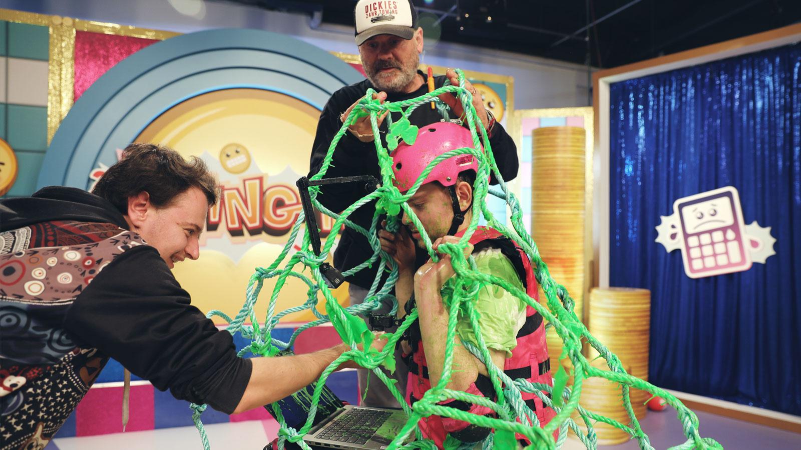 On set at the H&R Block shoot. A man in a pink helmet underneath a green net.