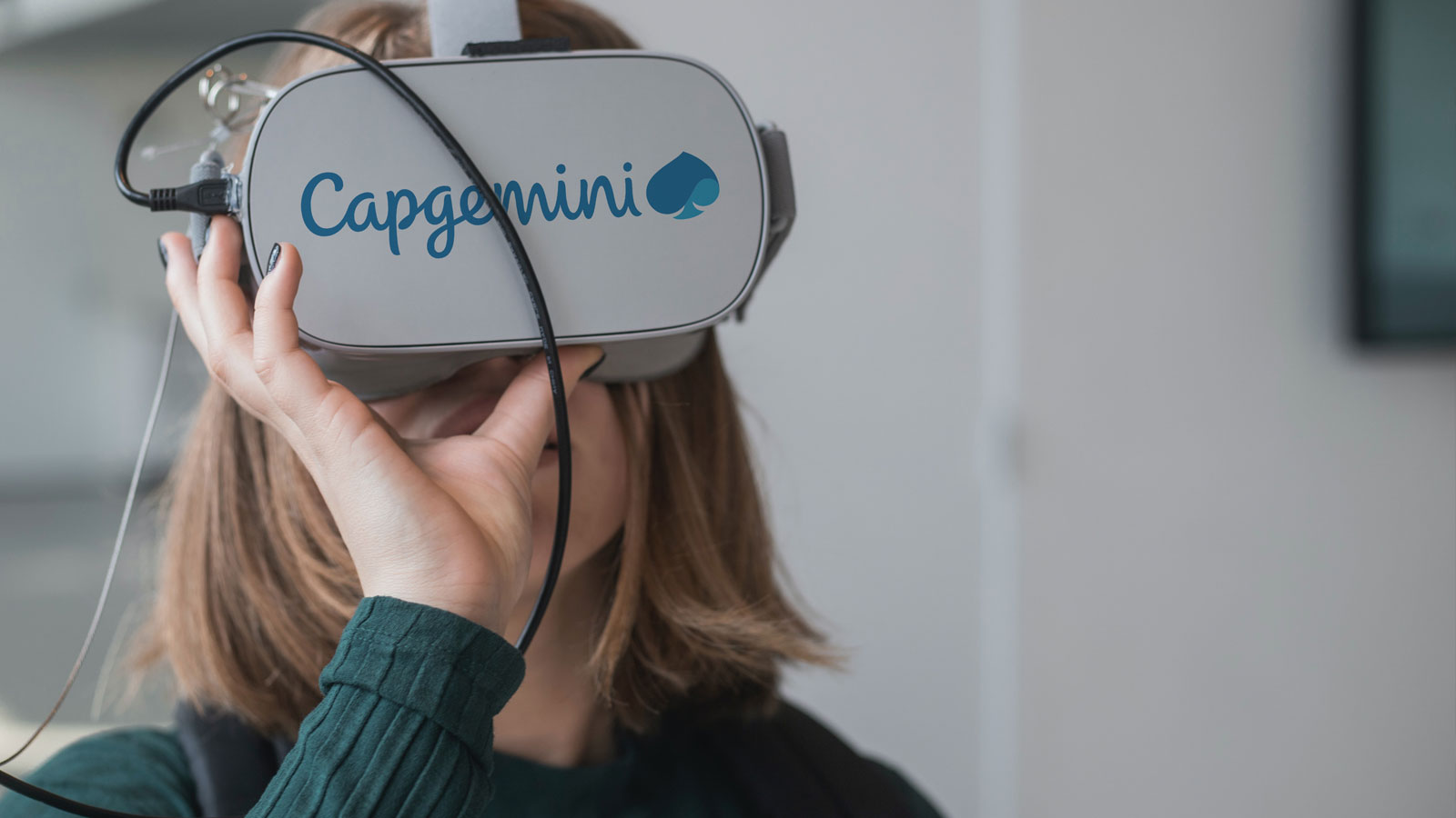 Lady using a VR headset with a Capgemini logo on it