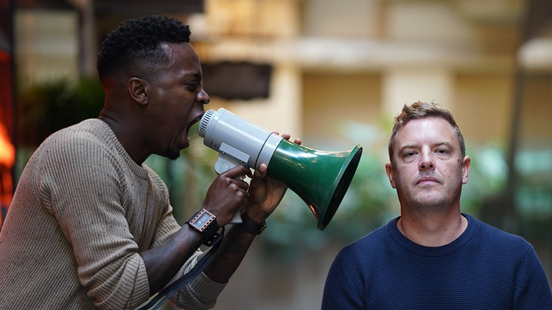 A Works employee pretending to shout into the ear of another employee with a megaphone