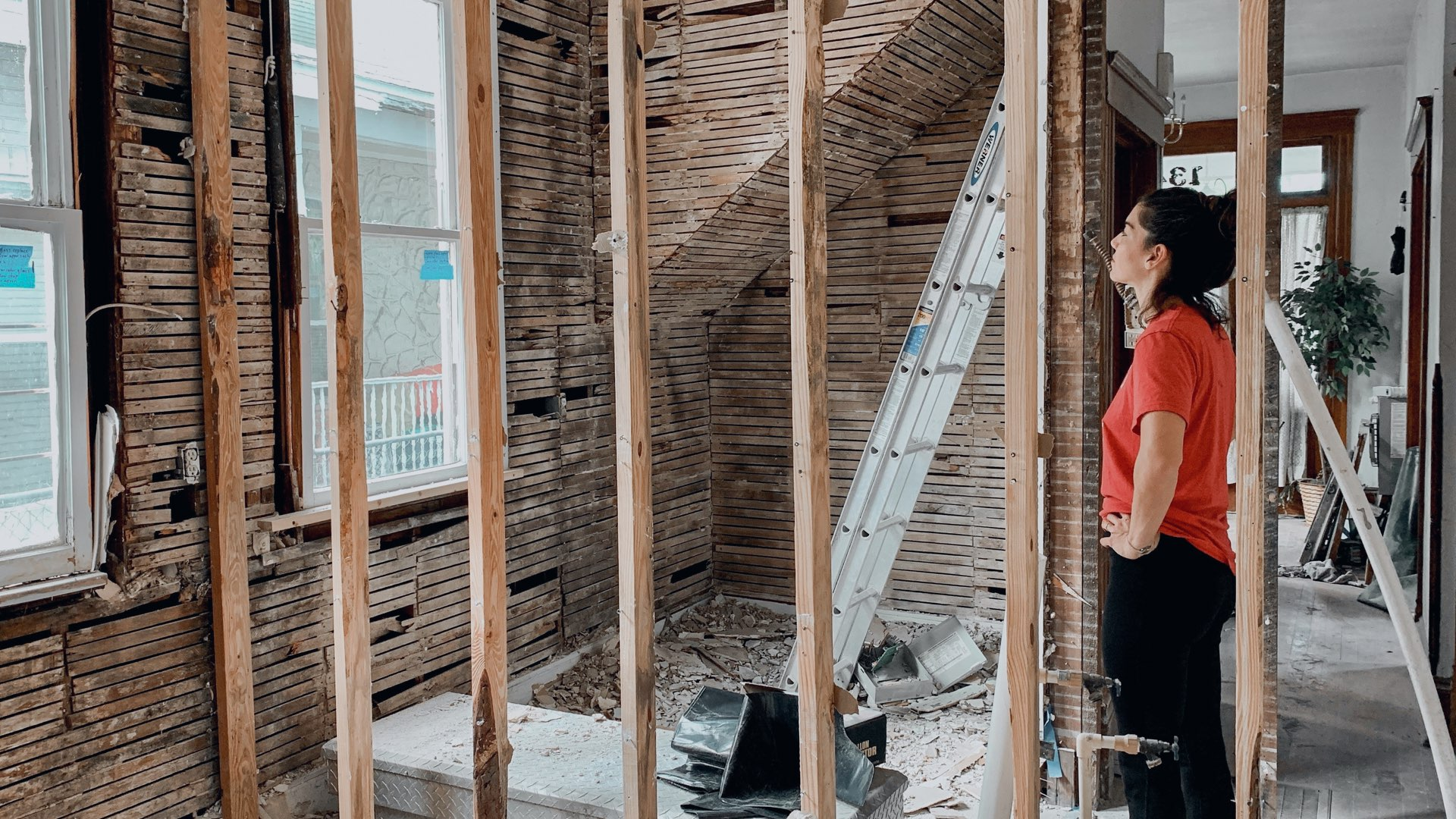 A young woman in a red shirt renovating her home