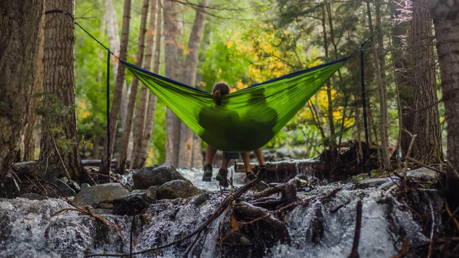 Digital Detoxing; Two people sitting in a hammock in the wilderness
