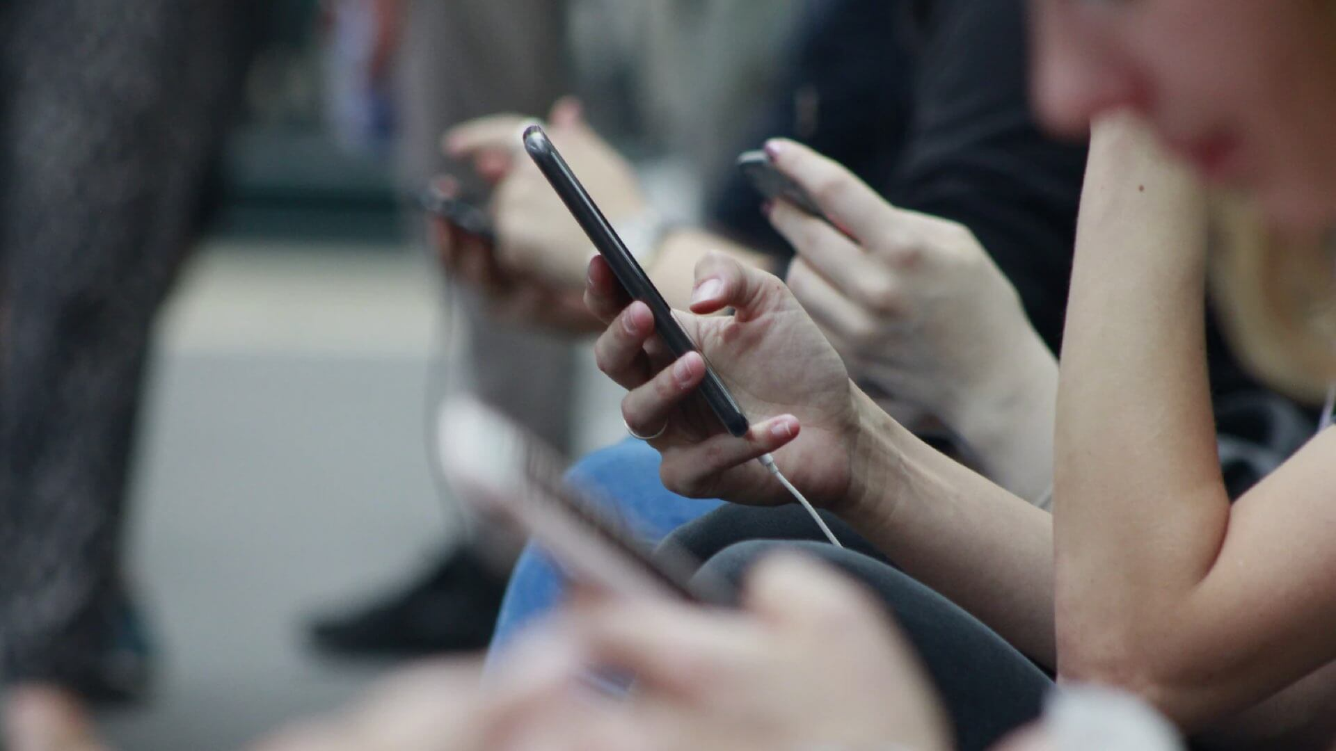 A queue of people seated outdoors, scrolling on their smart phones
