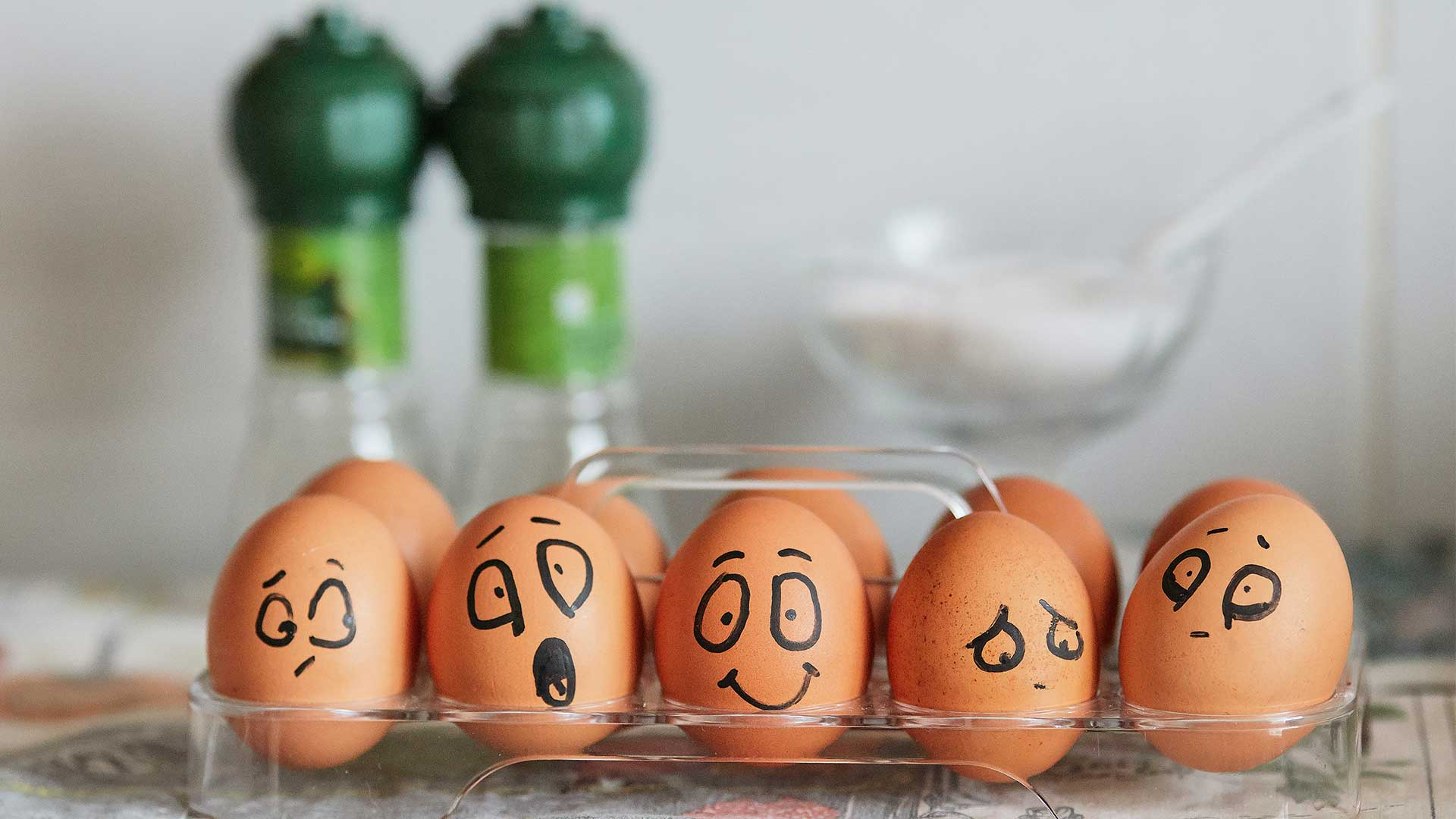 Eggs with various facial expressions drawn on them with a marker