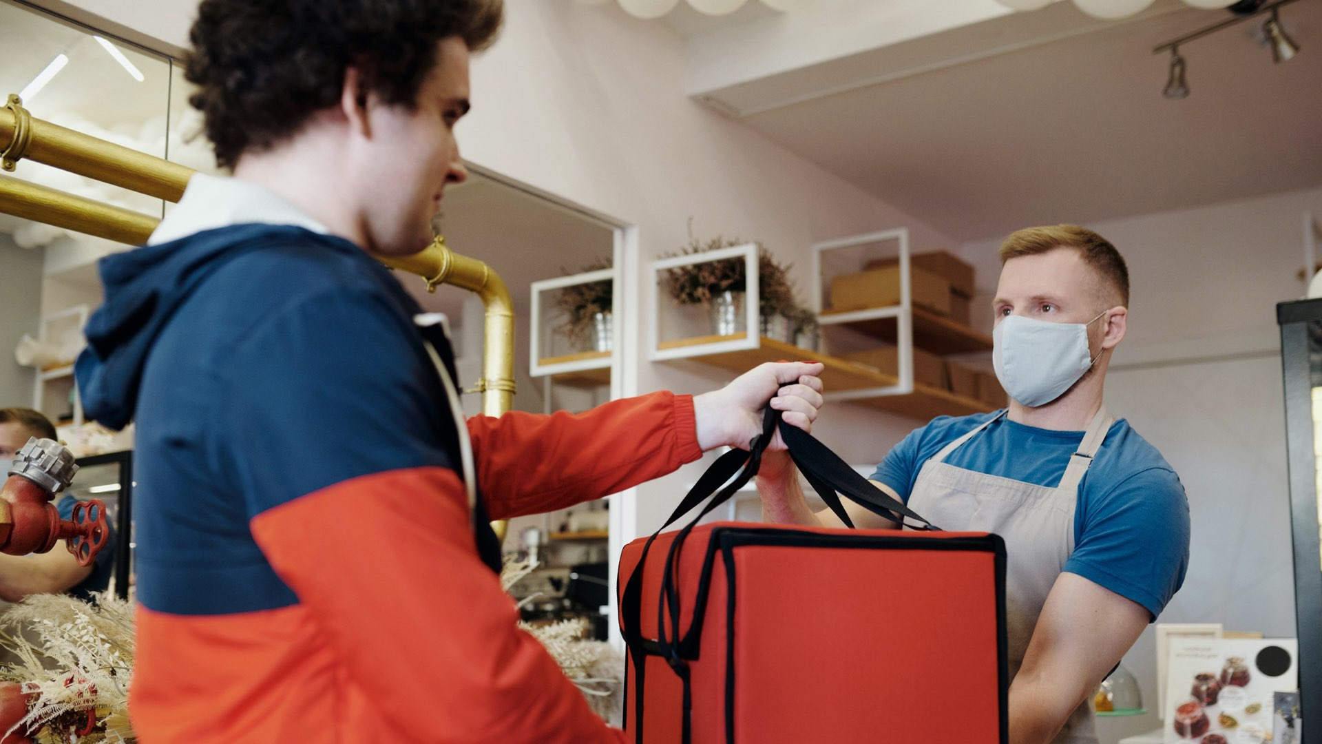 A shop owner handing a food delivery order over to the delivery rider in an insulated bag