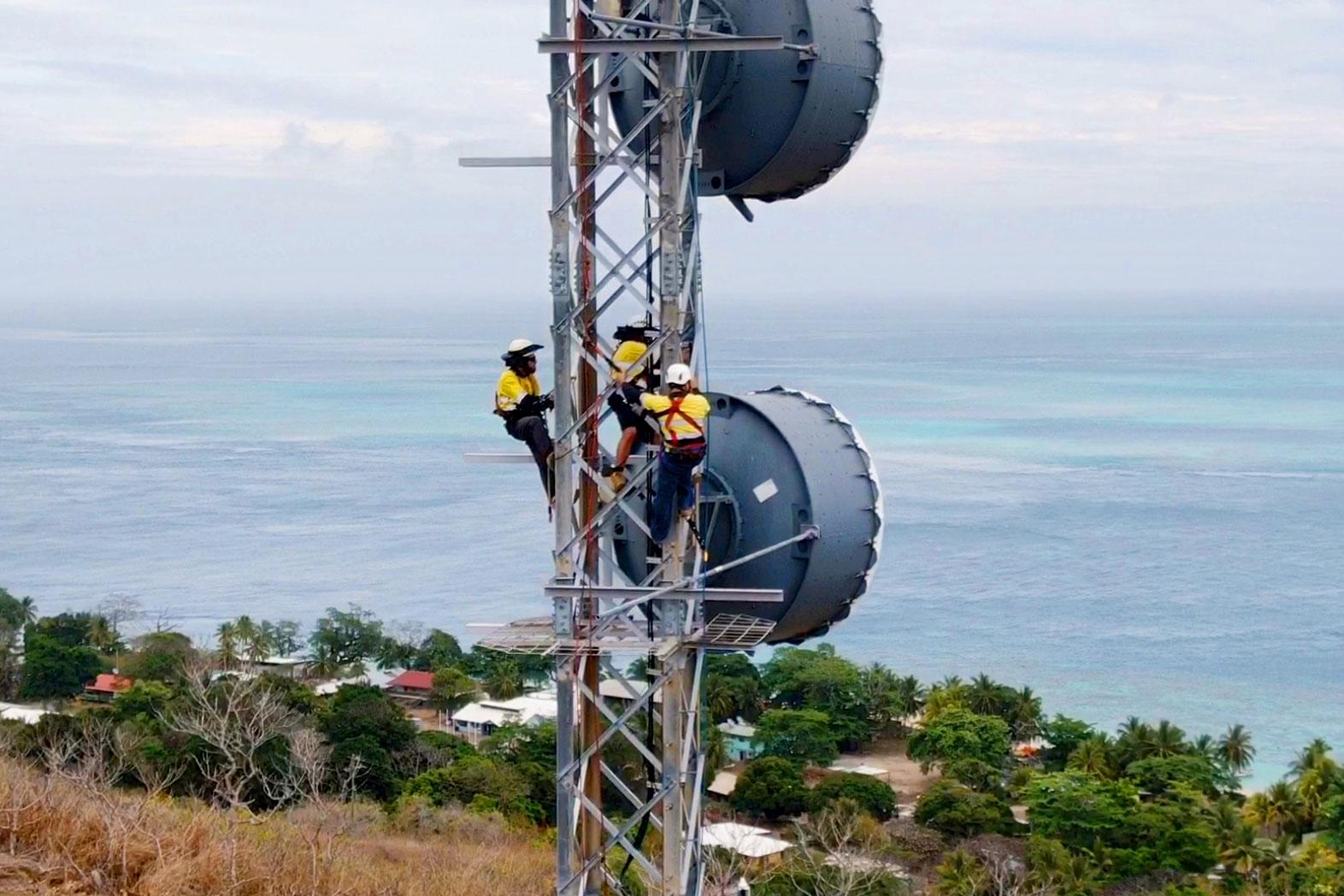 Three people working on an Amplitel tower