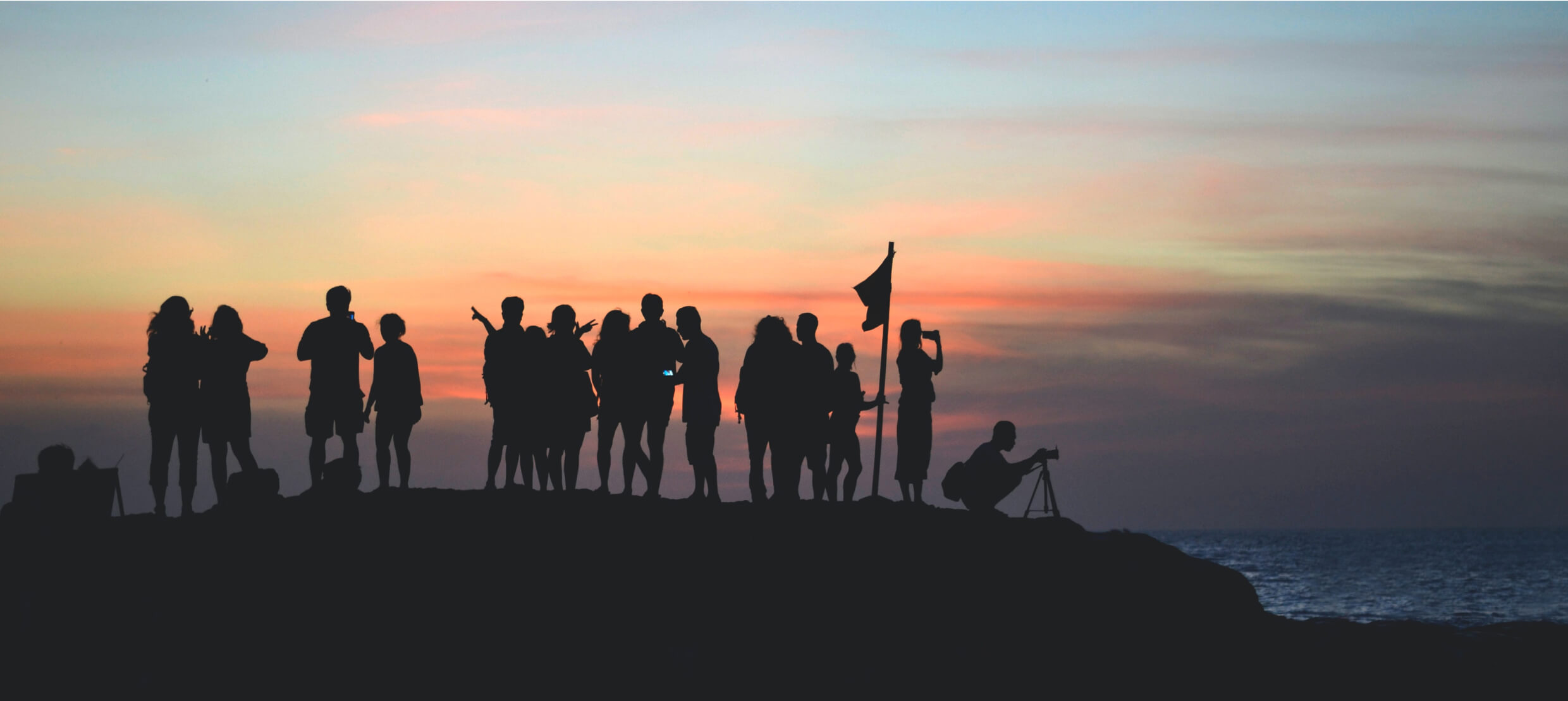 The silhouettes of a group of people standing near a body of water at sunset.