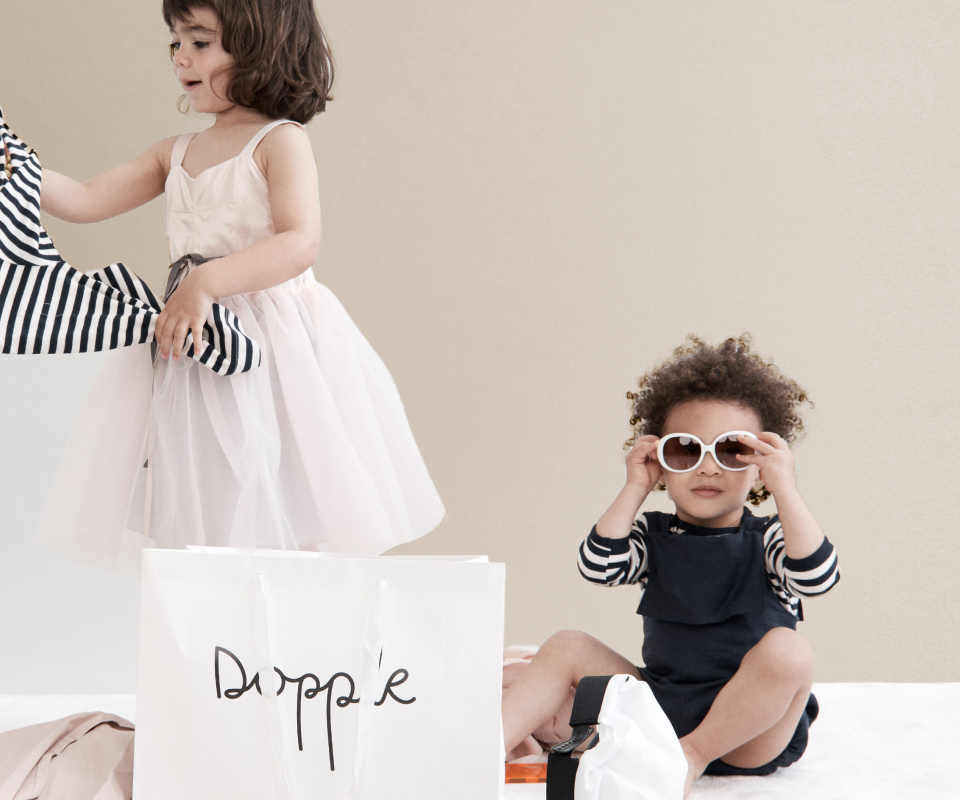 Two children try on their new clothes from Dopple.