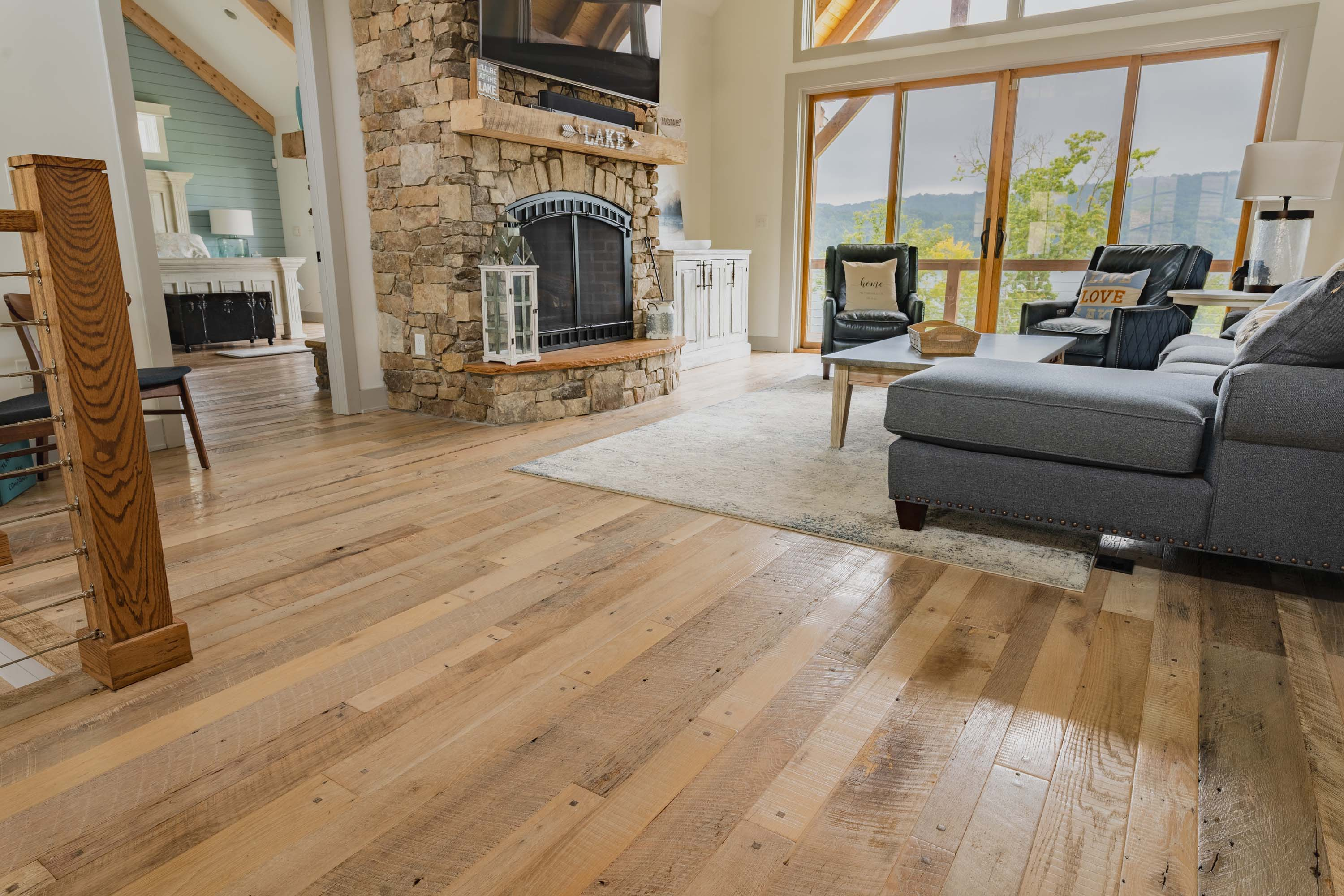 A living room and kitchen area in a house with Nantucket Reclaimed Wood Flooring by Tennessee Wood Flooring. These floors are real hardwood floors made locally.